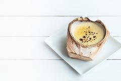 Kokosowy Creme Brulee jest cukierkowymi smakami na białym drewnianym stołowym tle obraz royalty free