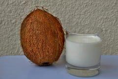 Kokosowy mleko z dużą brąz dokrętką obok białego tła zdjęcia stock