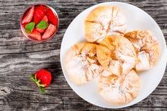 Koks i truskawkowi ptysiowi ciasta na białym naczyniu Zdjęcia Royalty Free