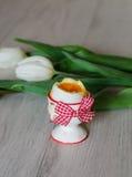 Kokt ägg i äggkopp med tulpan Arkivfoto