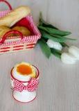 Kokt ägg i äggkopp med tulpan och bröd Royaltyfria Foton