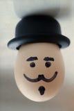Kokt äggtecken Ägg med en mänsklig framsida (retro stil, gammal pappers- bakgrund, mjuk fokus) Arkivfoto