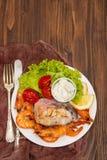 Kokt fisk med räkor och sallad på den vita maträtten Fotografering för Bildbyråer