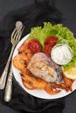 Kokt fisk med räkor och sallad på den vita maträtten Royaltyfri Fotografi