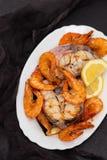 Kokt fisk med räkor och sallad på den vita maträtten Royaltyfri Foto