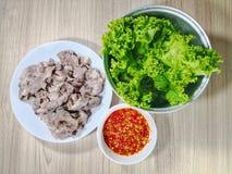 Kokt griskött som skivas med grönsallat och kryddig chilisås arkivfoto