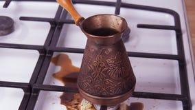 Kokt kaffe på gasugnen På gasugnen är en koppar den inristade turken med ett rinnande kaffe Rinnande kaffeslut upp Smutsigt G stock video