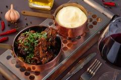 Kokt kalvkött med mosade potatisar i pannan Dekorerat med persilja och tjänat som med vin Royaltyfri Bild