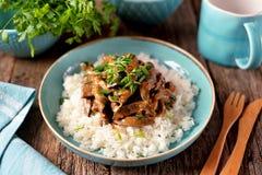 Kokt lever i en sås med löken, morot och persilja och kokta ris arkivbilder