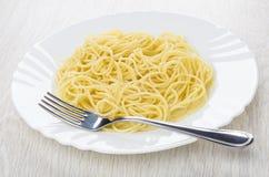 Kokt spagetti i den vita plattan, gaffel på tabellen royaltyfria foton