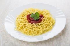 Kokt spagetti med ketchup och koriander i den vita plattan arkivfoton