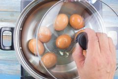 Kokta ägg för kockmatlagning i kruka royaltyfri bild