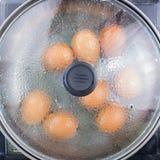 Kokta ägg för kockmatlagning i kruka arkivfoto