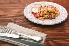 Kokta ägg i ett lager av korvkött som slås in med pasta Royaltyfria Foton