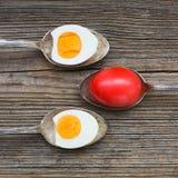 Kokta ägg i gamla skedar på gammal träbakgrund Royaltyfri Foto