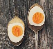 Kokta ägg i gammal sked på gammal träbakgrund Royaltyfria Bilder