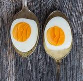 Kokta ägg i gammal tappningsked på gammal träbakgrund Arkivbild