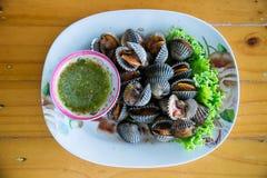 Kokta bubblor med varm och kryddig sås, lokal meny från havsskal Halv-lagad mat råkost Royaltyfria Bilder