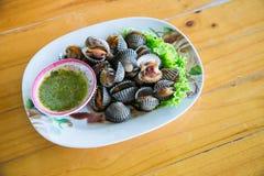 Kokta bubblor med varm och kryddig sås, lokal meny från havsskal Halv-lagad mat råkost Royaltyfri Fotografi