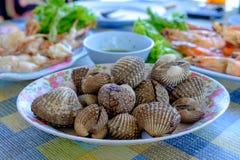 Kokta bubblor som tjänas som i plattan, är på tabellen tillsammans med annan mat Arkivfoton
