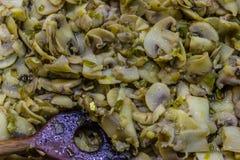 Kokta champinjoner med träskeden i dem Arkivbilder