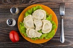 Kokta klimpar med grönsallat i plattan som är salt, peppar, tomat Royaltyfria Bilder
