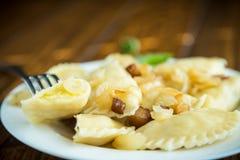 Kokta klimpar med potatisar och stekte lökar Arkivfoton
