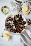 Kokta musslor och vitt vin på den vita stentabellen arkivbilder