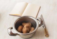 Kokta potatisar i en kastrull och en bok av recept Royaltyfria Foton