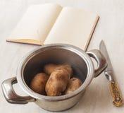 Kokta potatisar i en kastrull och en bok av recept Royaltyfri Foto
