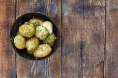 Kokta unga potatisar med dill och smör på en trätabell, bästa sikt, closeup Lantlig stil Royaltyfri Foto