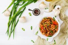 Kokta vita bönor med champinjoner och tomater Arkivfoto