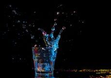 Koktajl w szkle z pluśnięciami na ciemnym tle Partyjna świetlicowa rozrywka Mieszany światło Obrazy Stock