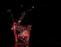 Koktajl w szkle z pluśnięciami na ciemnym tle Partyjna świetlicowa rozrywka Mieszany światło Obraz Stock