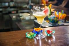 Koktajlu napój w żółtej przysłudze z kawałkiem arbuz na wierzchołku Zdjęcie Stock