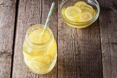 Koktajlu słój lemoniady i kostek lodu kruszki na drewnianym stołowym tle Fotografia Stock