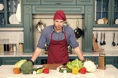 Koktribune bij keukenlijst Mens in chef-kokhoed en schort in keuken Groenten en hulpmiddelen klaar voor het koken van schotels royalty-vrije stock afbeeldingen