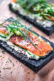 Kol bröd rökte Salmon Sandwiches på det wood brädet Arkivbild