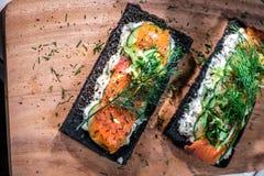 Kol bröd rökte Salmon Sandwiches på det wood brädet Arkivbilder