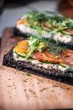 Kol bröd rökte Salmon Sandwiches på det wood brädet Royaltyfria Bilder