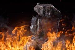 Kol klumpa sig med brandflammor arkivbild