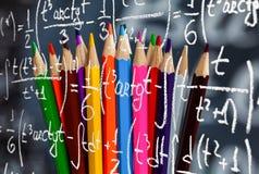 Kolaż Z powrotem szkoły tło składać się z kolorowi ołówki i matematyk formuły napiszą biel kredą dalej obraz royalty free