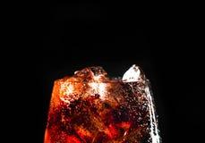 Kola en ijs in een glas op zwarte achtergrond Royalty-vrije Stock Afbeeldingen