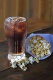Kola in glas met popcorn op houten achtergrond stock afbeeldingen
