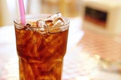Kola in het drinken van glas met ijs stock foto's