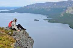 Kola Peninsula, Rusia, julio, 08, 2015 El turista se sienta al borde de un acantilado sobre el Seydozero en las tundras de Lovoze Imágenes de archivo libres de regalías