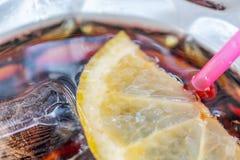 Kola refroidi à la glace avec la tranche de paille et de citron comme boisson régénératrice images libres de droits