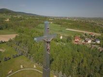 Kolaczyce, Pologne - peuvent 10, 2018 : Une statue énorme du Christ crucifié sur une colline au milieu des règlements signe relig Photos stock
