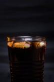 Kolaglas met ijsblokjes en druppeltjes, die op zwarte achtergrond worden geïsoleerd Royalty-vrije Stock Fotografie
