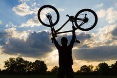 Kolarstwo sylwetki jeździec trzyma up z bicyklem fotografia royalty free